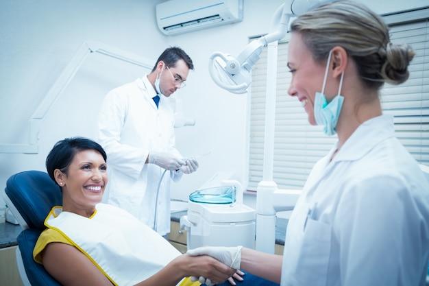 Vrouwelijke tandarts die handen met vrouw schudden