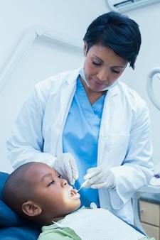 Vrouwelijke tandarts die jongenstanden onderzoekt