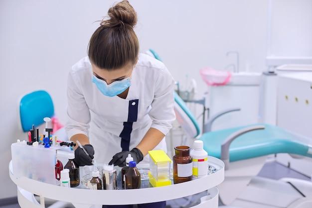 Vrouwelijke tandarts die met medische materialen en speciale professionele hulpmiddelen op werktafel werkt
