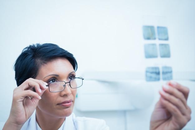 Vrouwelijke tandarts die röntgenstraal bekijkt