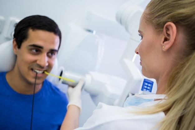 Vrouwelijke tandarts die röntgenstraal van patiëntentanden nemen