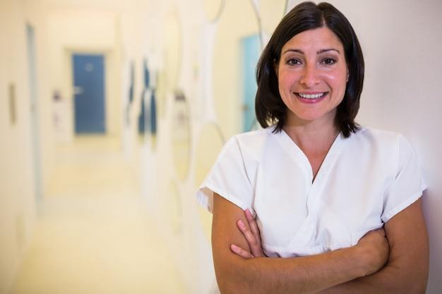 Vrouwelijke tandarts die zich met gekruiste handen bevindt