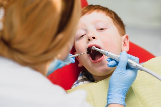 Vrouwelijke tandarts en kind in het kantoor van een tandarts