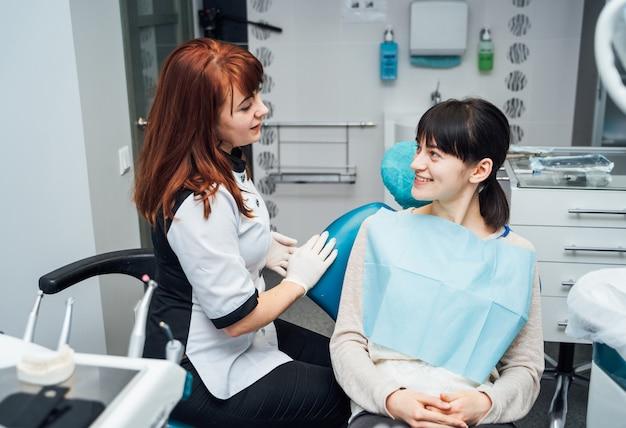 Vrouwelijke tandarts en patiënt in tandartsbureau.
