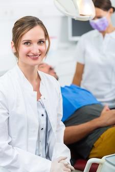 Vrouwelijke tandarts in haar operatie kijken naar de kijker, op de achtergrond geeft haar assistent een mannelijke patiënt een behandeling