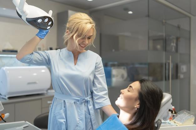 Vrouwelijke tandarts in tandheelkundige kliniek onderzoek en behandeling van mondholte voor patiënt.