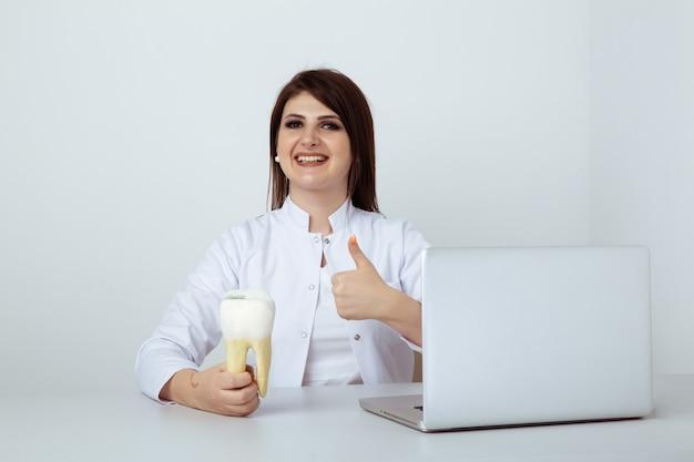 Vrouwelijke tandarts in uniform aan de balie zitten en werken met tandheelkundig personeel op kantoor.