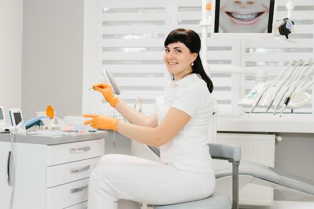 Vrouwelijke tandarts in witte jas op de werkplek