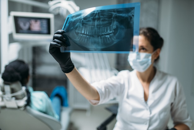 Vrouwelijke tandarts kijken op x-ray foto, tandheelkundige kliniek, patiënt in stoel op achtergrond. vrouw in tandheelkundekabinet, stomatologie, tandenzorg
