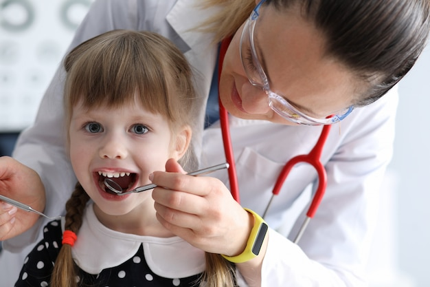 Vrouwelijke tandarts kijkt naar open mond weinig gelukkig meisje