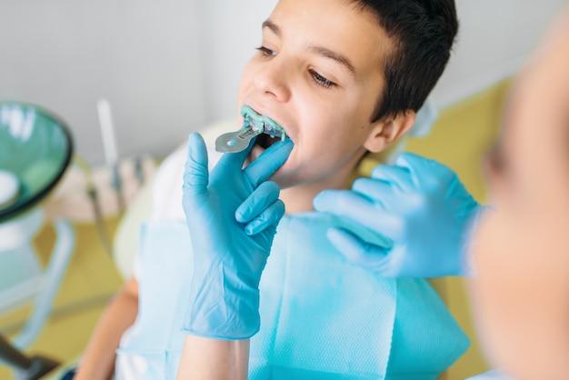 Vrouwelijke tandarts maakt tanden indruk