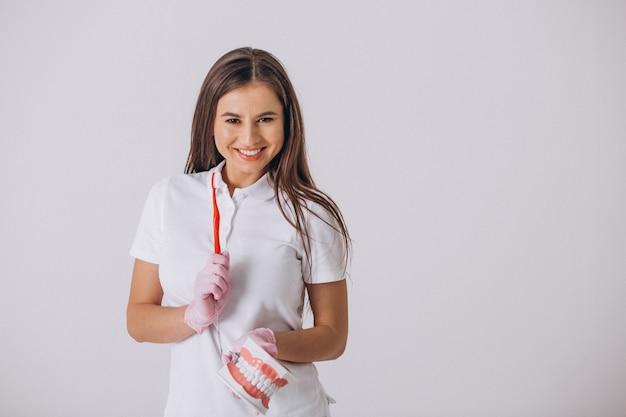 Vrouwelijke tandarts met geïsoleerde tandheelkundethulpmiddelen