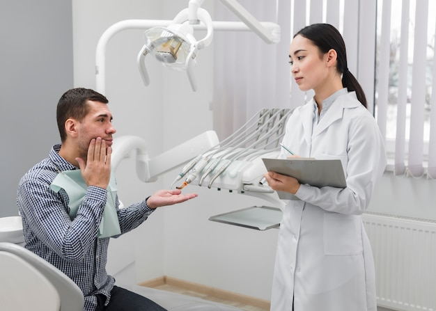 Vrouwelijke tandarts met patiënt