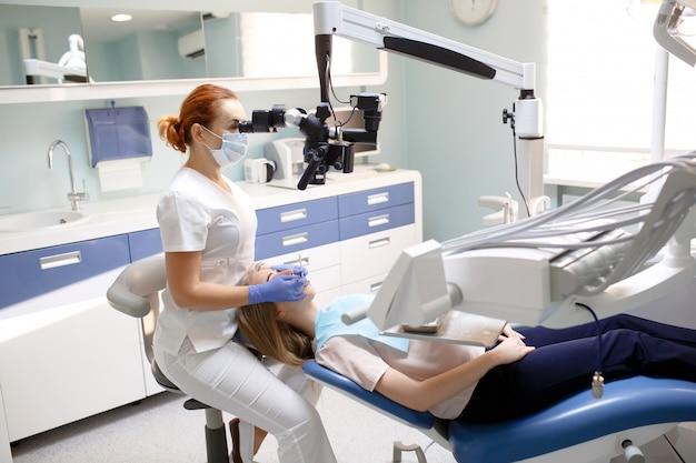 Vrouwelijke tandarts met tandhulpmiddelen - microscoop, spiegel en sonde die geduldige tanden behandelen op tandkliniekkantoor. geneeskunde, tandheelkunde en gezondheidszorgconcept. tandheelkundige apparatuur