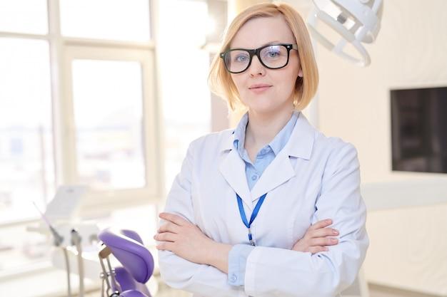 Vrouwelijke tandarts poseren in moderne kliniek