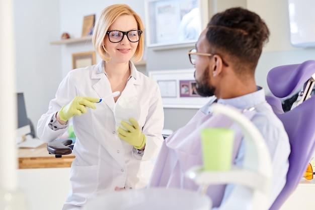 Vrouwelijke tandarts uitleggen hygiënevoorschriften