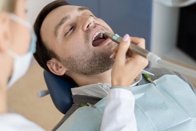 Vrouwelijke tandarts vullen holtes