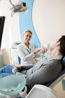 Vrouwelijke tandarts werken in moderne kliniek