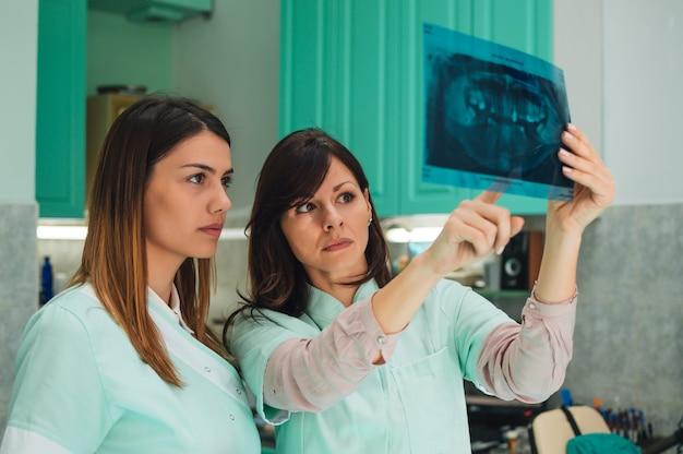 Vrouwelijke tandartsen die over röntgenstraal bespreken