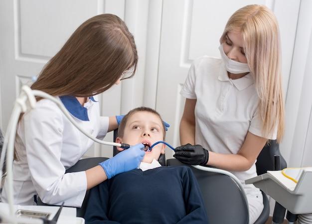 Vrouwelijke tandartsen die patiënt onderzoeken