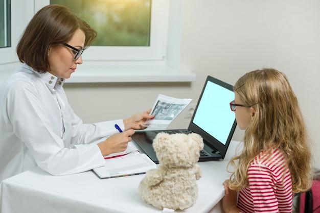 Vrouwelijke tandartsorthodontist met röntgenfoto die aan een kind spreekt.