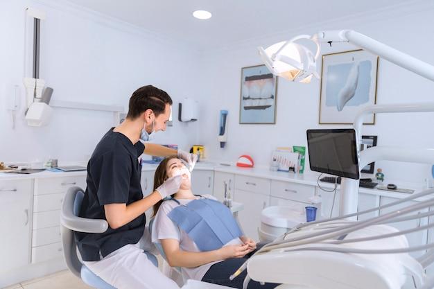 Vrouwelijke tanden die door mannelijke tandarts in kliniek worden gecontroleerd