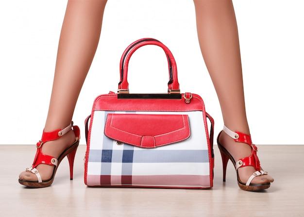 Vrouwelijke tas tussen de benen van de mooie vrouw in sandalen