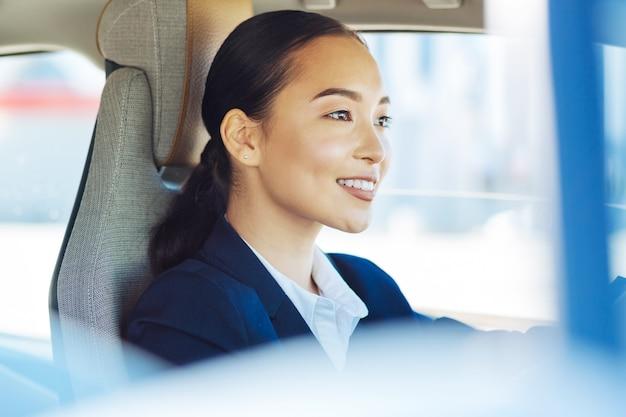 Vrouwelijke taxichauffeur. aangename jonge vrouw die tijdens het werk achter het stuur zit