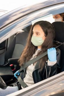 Vrouwelijke taxichauffeur in stoffen masker en latex handschoenen dragen veiligheidsgordel voor taxirit tijdens coronavirus pandemie