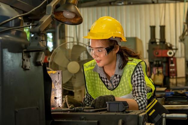 Vrouwelijke technicus die aan project in een fabriek werkt, industrieel de bouwconcept.