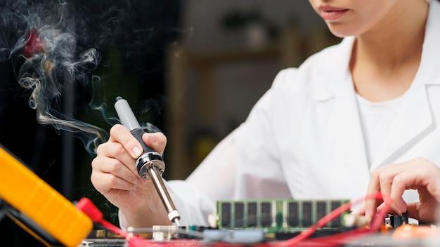 Vrouwelijke technicus met soldeerbout en elektronicabord