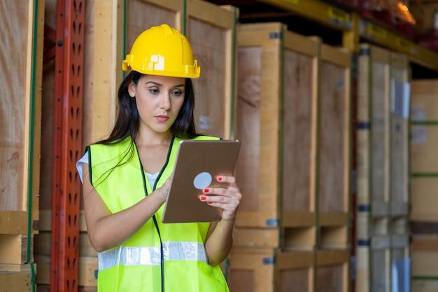 Vrouwelijke technicusarbeider gebruikt laptop en inspecteert de producten in een groot pakhuis.