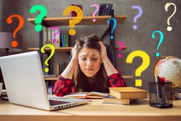 Vrouwelijke telewerker werkt thuis met een laptop met veel vragen.