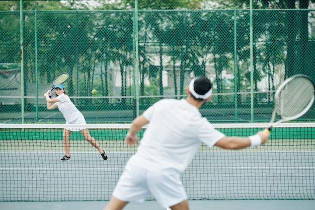 Vrouwelijke tennisspeelster die bal raakt