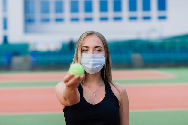Vrouwelijke tennisspeelster spelen met beschermend masker op de rechtbank
