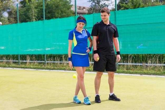 Vrouwelijke tennisspeelster tennisbal gooien in de buurt van haar partner, het dragen van een sportkleding met zwarte covers voor racket op hun schouders, op een veld buiten in de zomer of lente