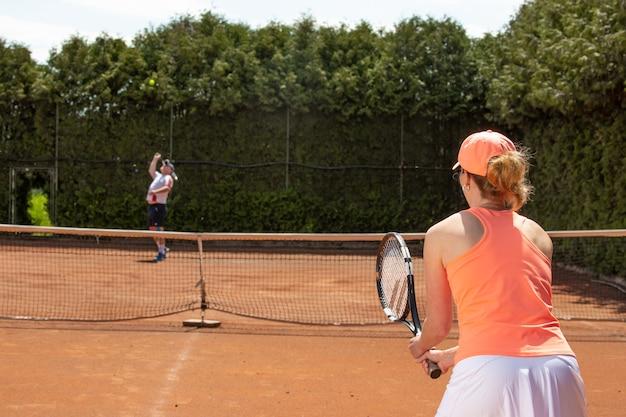 Vrouwelijke tennisspeelster training met trainer op de gravelbaan, sport concept