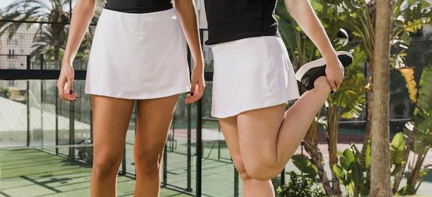 Vrouwelijke tennisspelers die voor spel voorbereidingen treffen