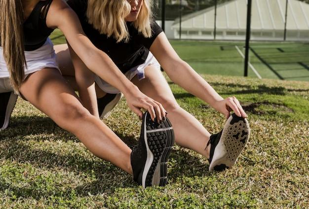 Vrouwelijke tennisspelers die zich in openlucht uitrekken