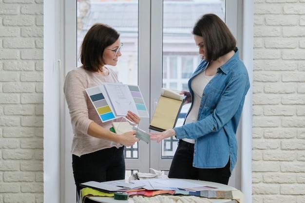 Vrouwelijke textielontwerper, decorateur en klant kijken paletten met stoffen