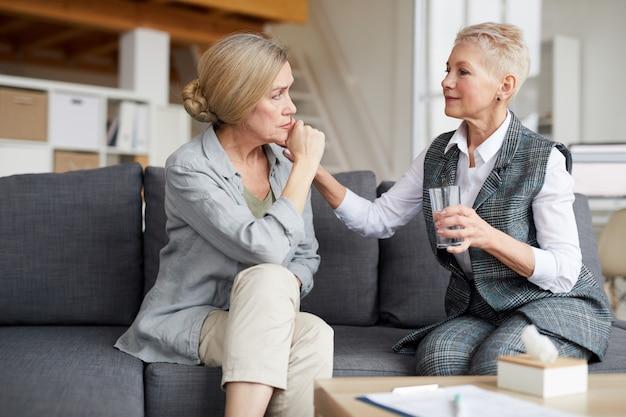 Vrouwelijke therapeut comforting senior patient