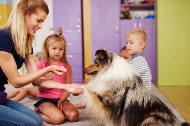 Vrouwelijke therapeut en haar hond in de kleuterschool