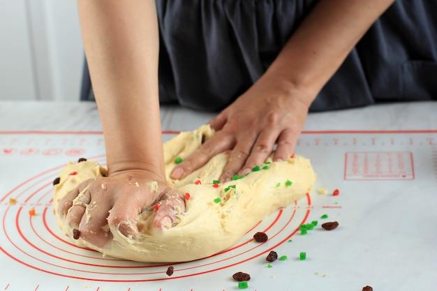 Vrouwelijke thuisbakker kneden brooddeeg met rozijnen en droog fruit, proces maken christmast stollen duits traditioneel brood