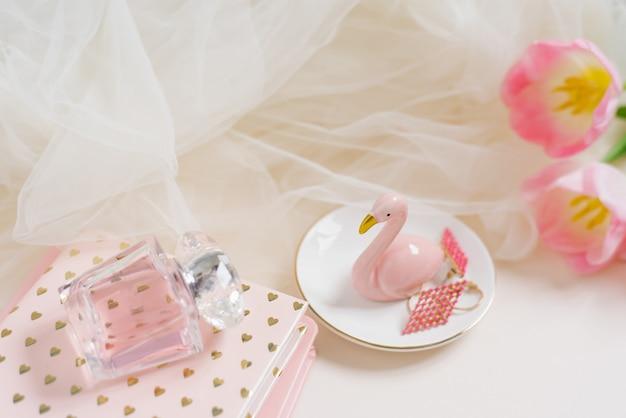 Vrouwelijke thuiskantoor bureau werkruimte met roze tulp bloemen notebook flamingo beeldje accessoires en cosmetica op beige achtergrond mode blog competitie