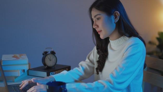 Vrouwelijke tiener die 's nachts online les aan de universiteit bijwoont, deelneemt aan de klas met behulp van laptop beantwoordt de vragen in de woonkamer thuis