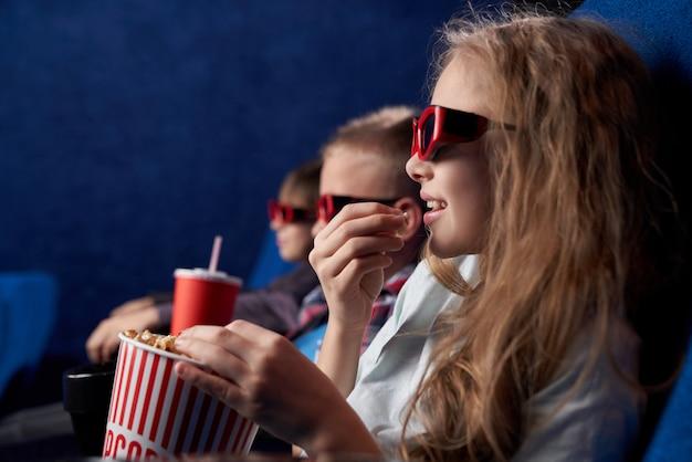 Vrouwelijke tiener in 3d glazen die met vrienden in bioskoop rusten