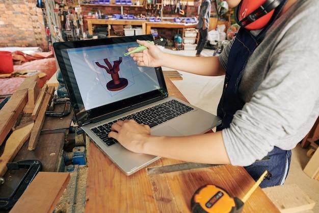 Vrouwelijke timmerman die 3d-model van eettafel op laptop maakt alvorens het te maken