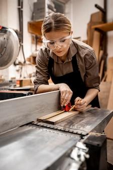 Vrouwelijke timmerman die in de studio met elektrische zaag werkt