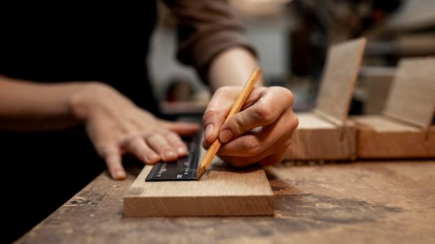 Vrouwelijke timmerman die in de studio met potlood werkt