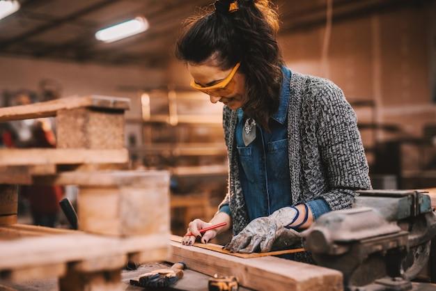 Vrouwelijke timmerman die in workshop werkt. vrouw doet mannelijke werk concept.